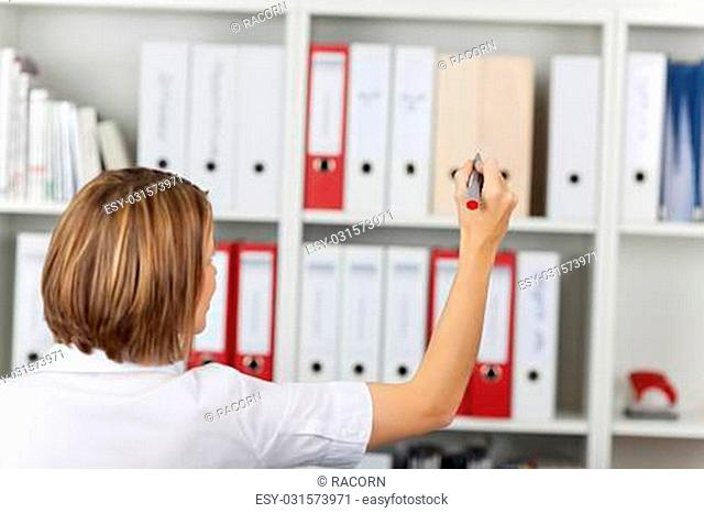 Female secretary write something on the stack of files at the shelf