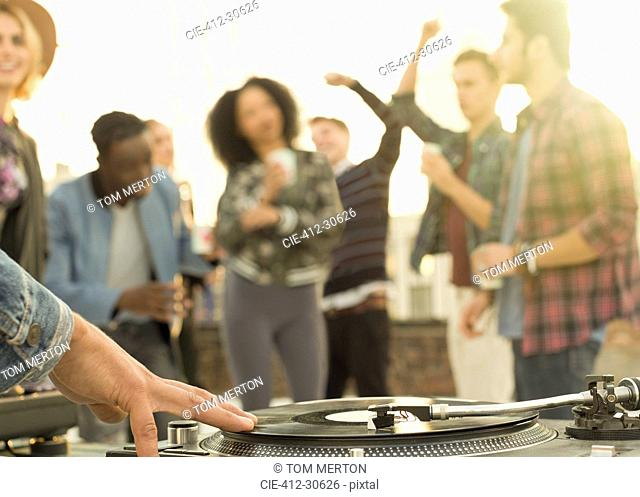 DJ spinning record at rooftop party