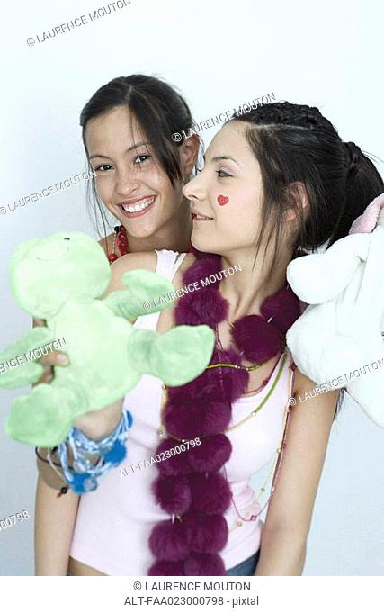 Two young female friends, one holding stuffed animals, looking at camera, portrait
