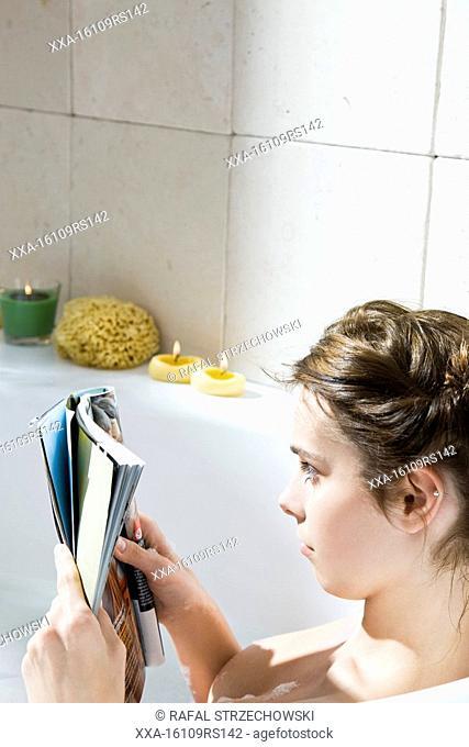 woman reading magazine in bath