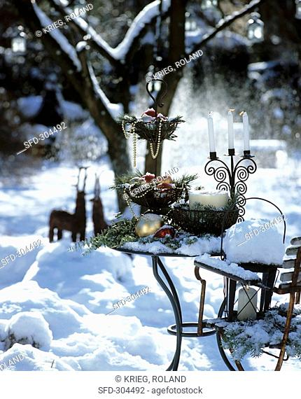 Table decorated for Christmas in snowy garden