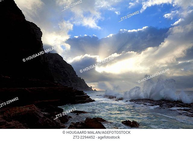 Landscape photo of a wave crashing against the rocks under a dramatic sunrise sky. Cape Point National Park, Cape Town, South Africa