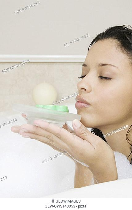Side profile of a teenage girl holding a soap dish