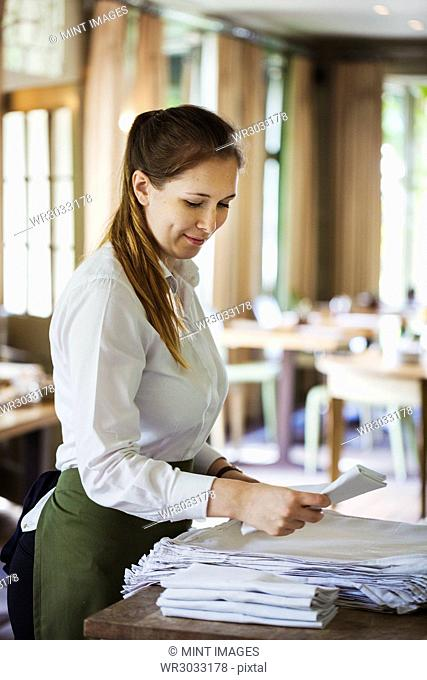 Woman wearing apron standing at a table in a restaurant, folding napkins