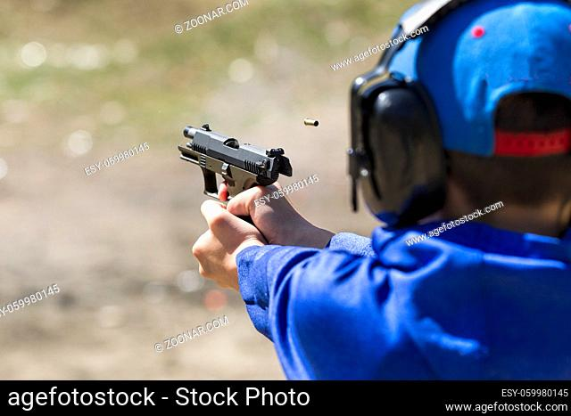 A boy safely practices shooting a pistol at a range in north Idaho