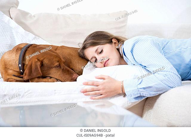 Young woman asleep with her dog on sofa
