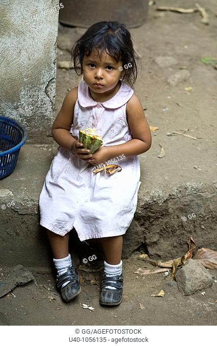 Young girl holding raw cacao pod
