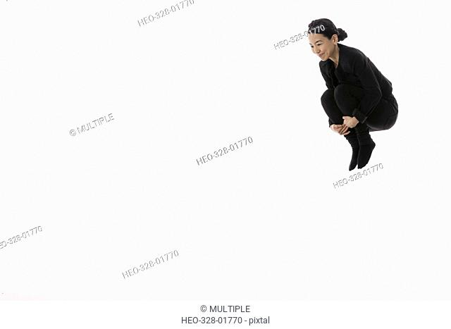 Confident businesswoman jumping, hugging knees against white background