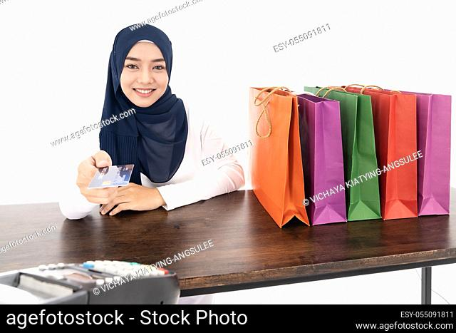 Confident happy smiling female muslim woman pay for her shopping with credit card with EDC machine using as consumerism and shopaholic concept