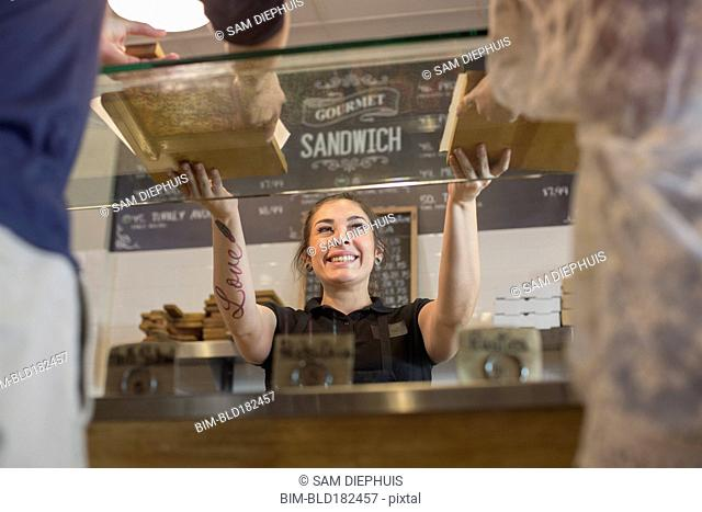 Server handing pizza to customers in cafe