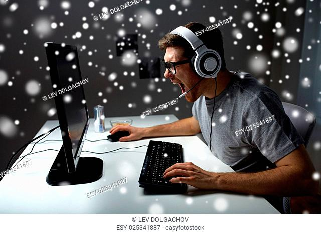 technology, gaming, entertainment, let's play and people concept - angry screaming young man in headset with pc computer playing game at home and streaming...