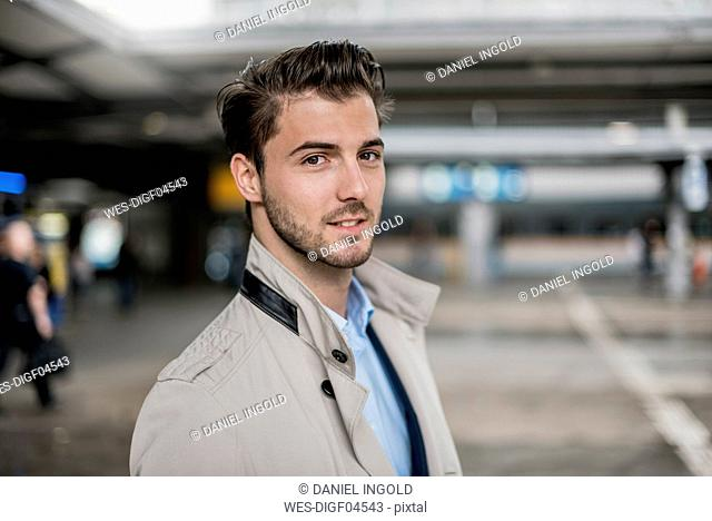 Portrait of smiling young businessman wearing a coat