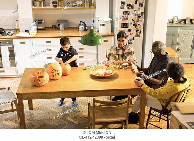 Grandparents watching grandchildren carving and painting Halloween pumpkins at dining table