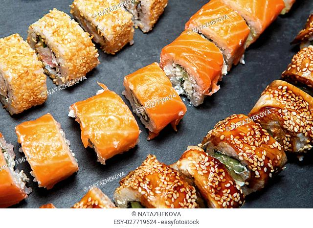 Philadelphia Roll, California Roll, Eel Avocado Roll on black slate tray background. Delicious rolls and sushi with eel, salmon, shrimp