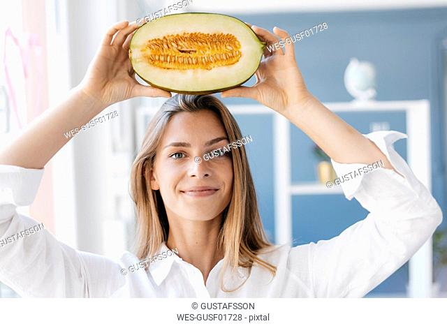 Young woman balancing half of a melon on her head