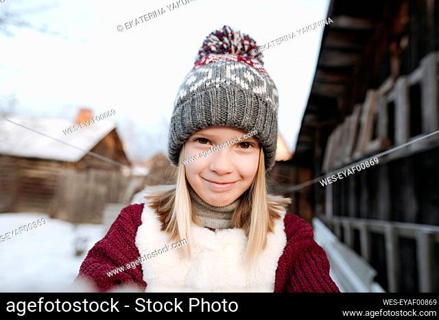 Portrait of smiling girl wearing woolly hat in winter