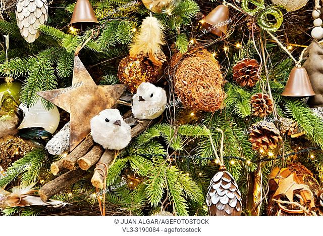 Background of fir tree branches with various cozy rustic decor and golden burning garland