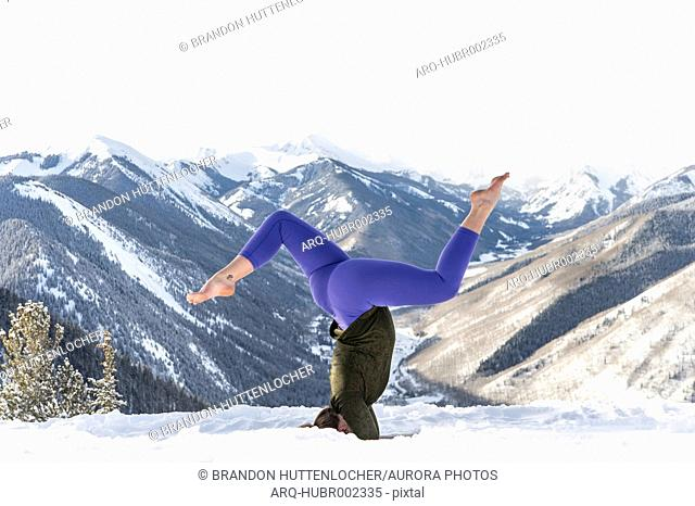 Young woman doing headstand on top of snowy hill against mountain valley, Aspen, Colorado, USA
