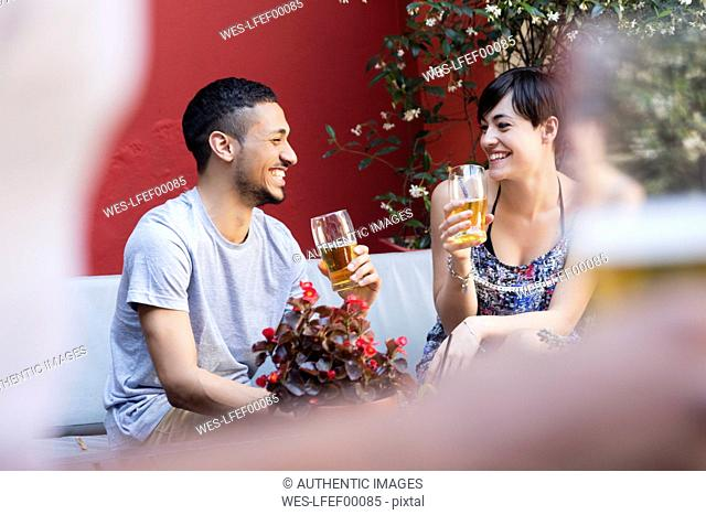 Happy couple having a beer outside