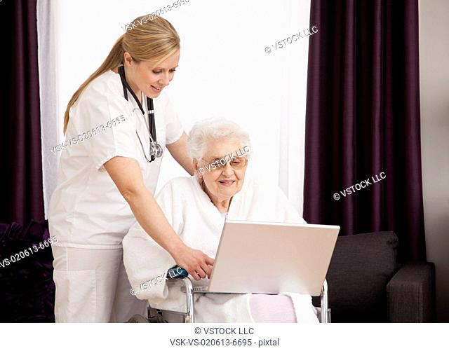Nurse helping senior woman on wheelchair in using laptop