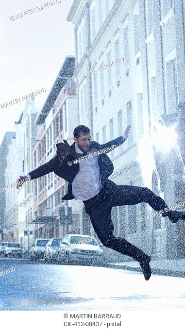 Businessman dancing in rainy street