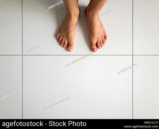 Man's feet on white ceramic tiles