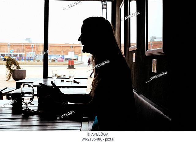 Side view of silhouette female customer sitting in cafe