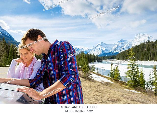 Caucasian couple reading map on car, Banff, Alberta, Canada
