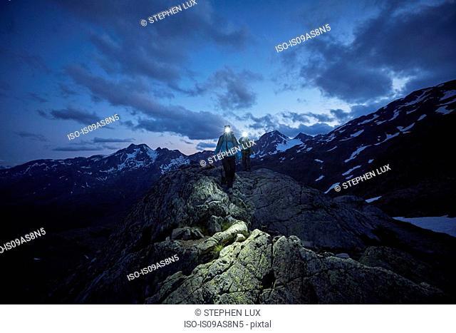 Young couple hiking at night wearing headlamps, Val Senales Glacier, Val Senales, South Tyrol, Italy