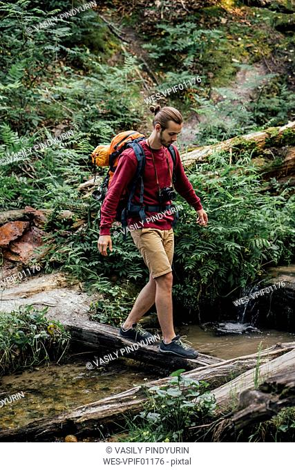Young hiker with backpack crossing water in the forest