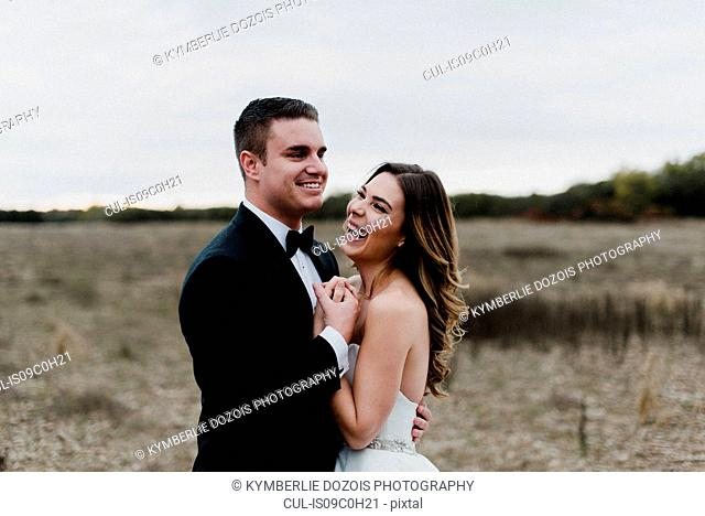 Happy young bride and groom hugging and laughing in field
