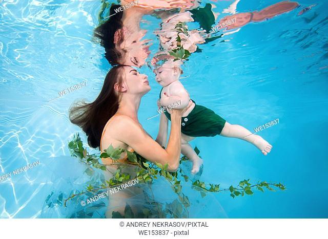 Woman in green dress with little boy posing under water in pool