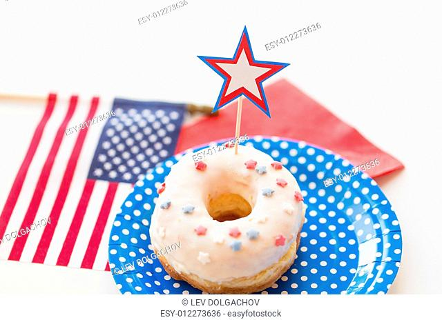 american independence day, celebration, patriotism and holidays concept - close up of glazed sweet donut with american flag and star decoration on disposable...