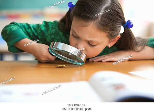 Caucasian girl using magnifying glass in classroom