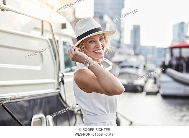 Portrait of happy young woman wearing a hat at a marina next to a yacht