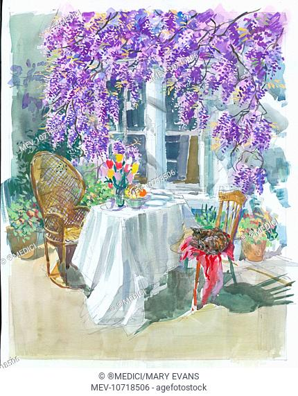 Garden table with wisteria, table with white cloth and vase of flowers