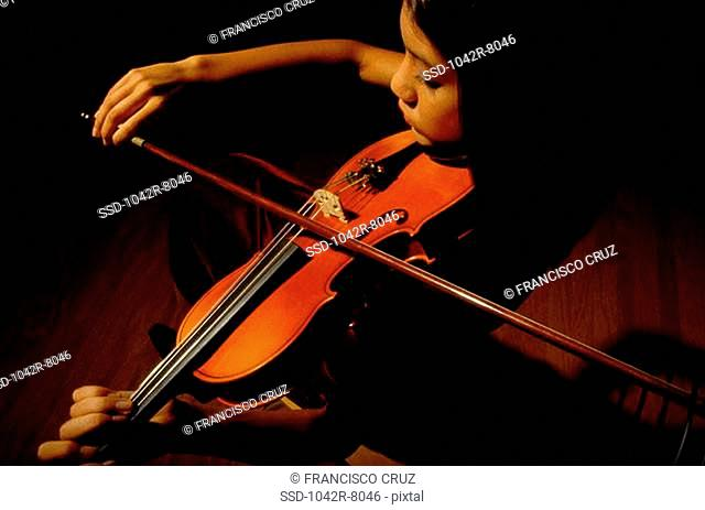 High angle view of a young woman playing the violin