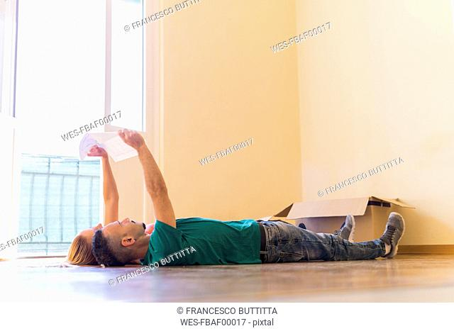 Couple lying side by side on the floor of new home looking together at contract