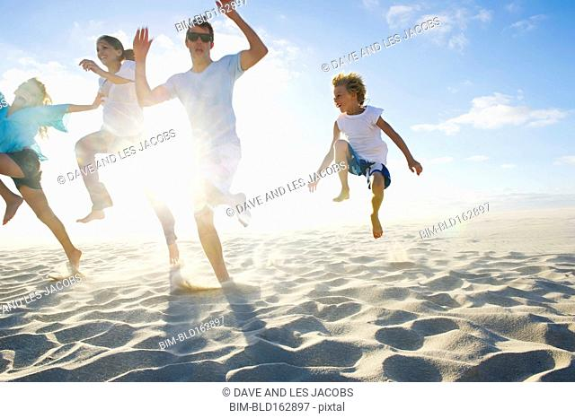 Caucasian parents and children jumping for joy on beach