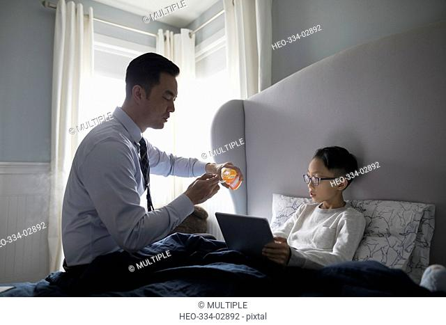 Businessman father serving cough syrup for sick son in bed with digital tablet