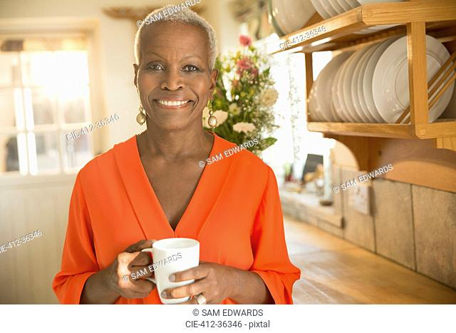 Portrait smiling senior woman drinking coffee in kitchen