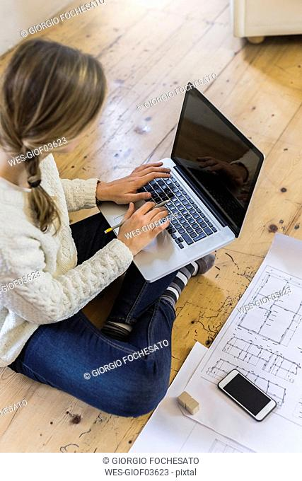 Woman sitting on the floor with blueprint using laptop