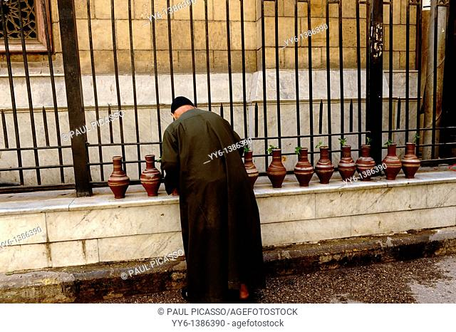 imam filling up water bottles, outside the Al-Hussein Mosque , which sits on the site of the cemetery of the Fatimid caliphs , islamic cairo, cairo, egypt