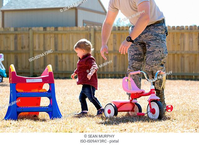 Young male soldier playing with toddler daughter in garden at air force military base
