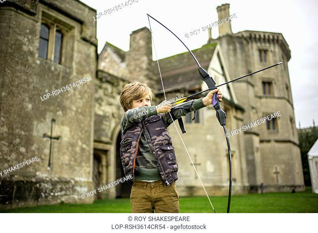 England, Gloucestershire, Thornbury. A young boy in Thornbury Castle garden playing archery