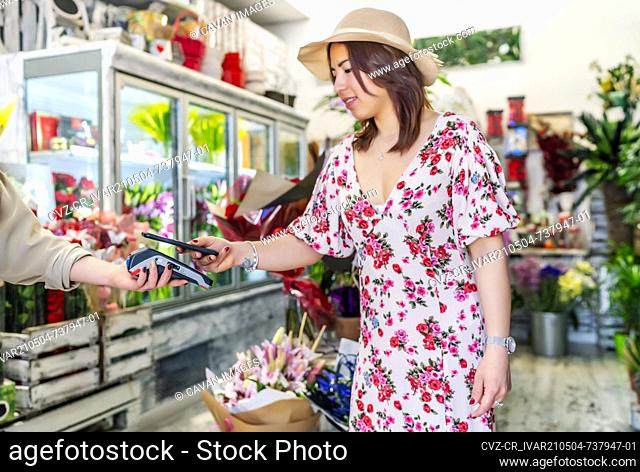 elegant woman paying with her mobile phone