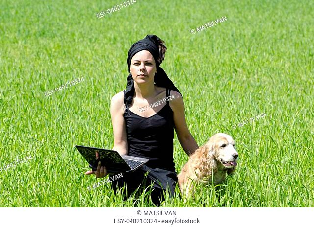 Woman sitting down on the green grass with a computer and her dog