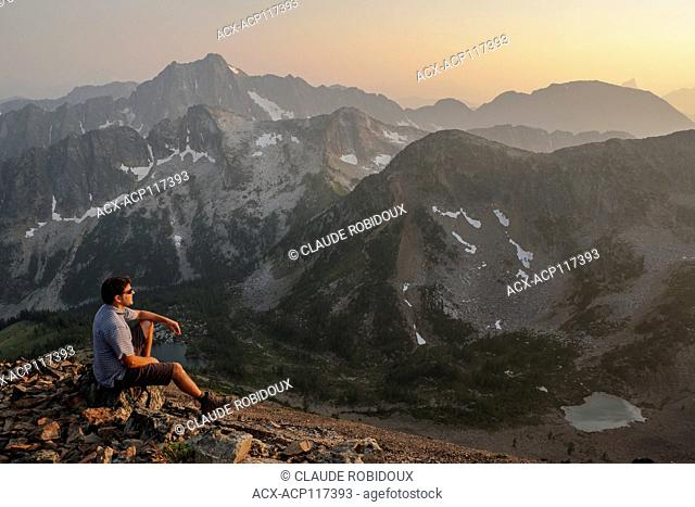 Hiker watching the sunset over the Cascade Mountains at the summit of Frosty Mountain in Manning provincial park, British Columbia, Canada