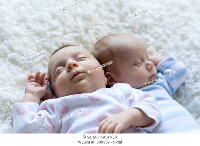Portrait of sleeping newborn baby girl lying besides her twin brother