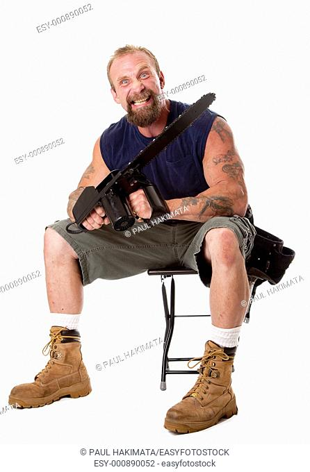 Crazy Caucasian man with tattoos and chainsaw sitting on stool with strong facial expression, isolated